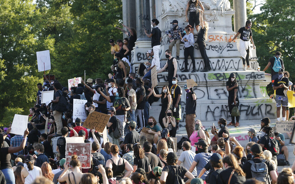 FILE - This Tuesday, June 2, 2020 file photo shows a large group of protesters gather around the statue of Confederate General Robert E. Lee on Monument Avenue near downtown in Richmond, Va. Virginia Gov. Ralph Northam announced plans Thursday, June 4, for the removal of the iconic statue. (AP Photo/Steve Helber, File)