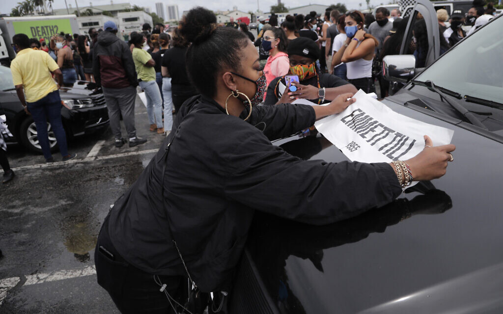 A demonstrator places an Emmett Till sign on a vehicle before a police escorted funeral procession to symbolize a day of mourning for those lives lost due to systemic racism, Wednesday, June 3, 2020, in Hallandale Beach, Florida. (AP Photo/Lynne Sladky)