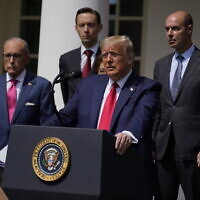 US President Donald Trump speaks during a news conference in the Rose Garden of the White House, Friday, June 5, 2020, in Washington. White House chief economic adviser Larry Kudlow, left, and Labor Secretary Eugene Scalia, top right listen. (AP Photo/Evan Vucci)