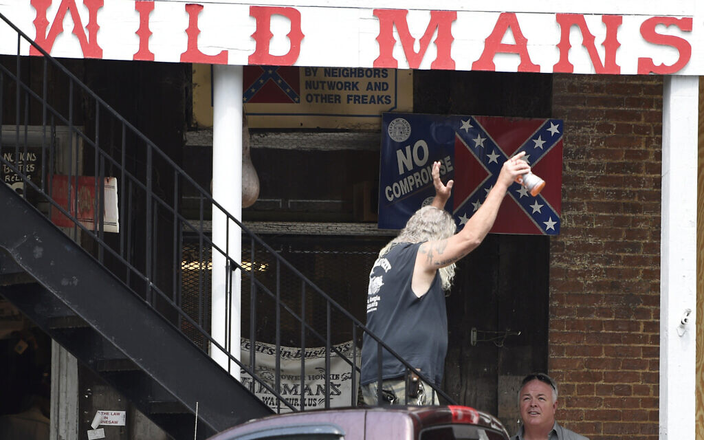 A patron of a Confederate memorabilia store reacts to protesters, Friday, June 5, 2020, in Kennesaw, Georgia. (AP Photo/Mike Stewart)