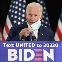 Democratic US presidential candidate, former vice president Joe Biden, takes off his mask before speaking during an event in Dover, Delaware, June 5, 2020. (AP Photo/Susan Walsh)