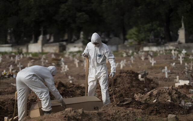 Cemetery workers in protective clothing maneuver the coffin of 57-year-old Paulo Jose da Silva, who died from the new coronavirus, in Rio de Janeiro, Brazil,  June 5, 2020. According to Monique dos Santos, her stepfather mocked the existence of the virus, didn't use a mask, didn't take care of himself, and wanted to shake hands with everybody (AP Photo/Leo Correa)