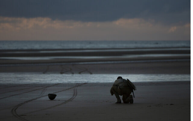 A man in a vintage US WWII uniform kneels at sunrise prior to a D-Day 76th anniversary ceremony in Saint Laurent sur Mer, Normandy, France, June 6, 2020 (AP Photo/Virginia Mayo)