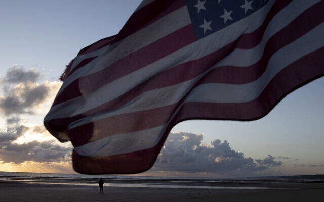 A man in a vintage US WWII uniform walks at sunrise prior to a D-Day 76th anniversary ceremony in Saint Laurent sur Mer, Normandy, France, June 6, 2020 (AP Photo/Virginia Mayo)