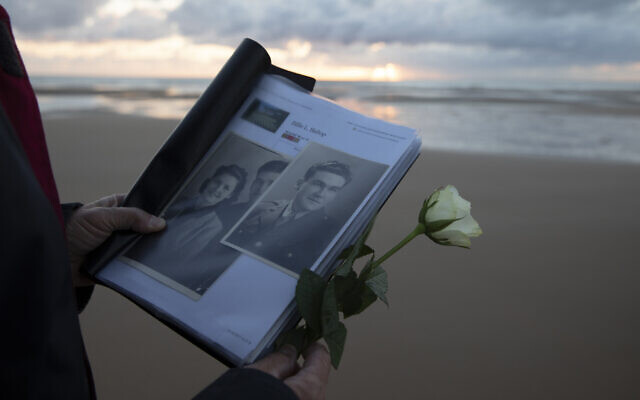 Billie Bishop, from San Jose, California, holds a photo of his uncle, WWII soldier Billie Bishop, as he prepares to lay a rose in the sea during a D-Day 76th anniversary ceremony in Saint Laurent sur Mer, Normandy, France,  June 6, 2020 (AP Photo/Virginia Mayo)
