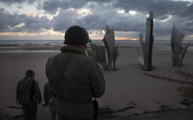 Two men in vintage US WWII uniforms walk toward the Les Braves monument at sunrise prior to a D-Day 76th anniversary ceremony in Saint Laurent sur Mer, Normandy, France, June 6, 2020 (AP Photo/Virginia Mayo)