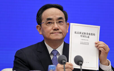 Xu Lin, vice head of the Publicity Department of the Communist Party, shows a copy of the white paper on fighting COVID-19 China in action during a press conference at the State Council Information Office in Beijing, June 7, 2020 (AP Photo/Andy Wong)