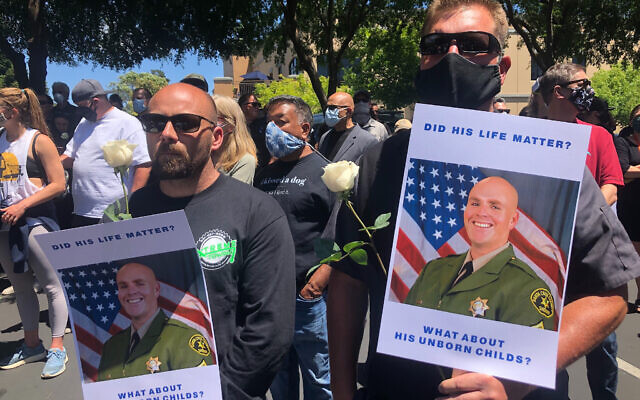 Matthew Rose, left, and Michael Carr, of Santa Cruz County hold posters of slain Sgt. Damon Gutzwiller, as they join others outside the Santa Cruz County Sheriff-Coroner's Office to pay their respects in Santa Cruz, Calif., Sunday, June 7, 2020.  (AP Photo/Martha Mendoza)