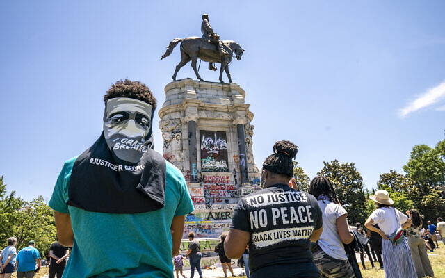 People gather at the Robert E. Lee Monument, now covered by protest graffiti, in Richmond, Virginia, June 7, 2020, following a week of unrest in the US against police brutality and racism in policing (AP Photo/J. Scott Applewhite)