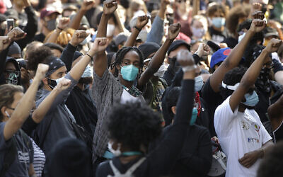 Demonstrators raise their arms during a protest against police brutality,  in Boston, June 10, 2020. (Steven Senne/AP)