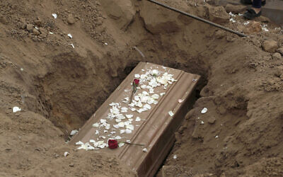The remains of Nolberto Albina, who family members say died of COVID-19-related complications, are buried at the Martires 19 de Julio cemetery on the outskirts of Lima, Peru, June 17, 2020.  (AP Photo/Martin Mejia)