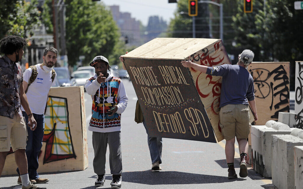 Protesters move a plywood box to further blockade a street adjacent to a closed Seattle police precinct Thursday, June 18, 2020, in Seattle, in what has been named the Capitol Hill Occupied Protest zone. (AP Photo/Elaine Thompson)