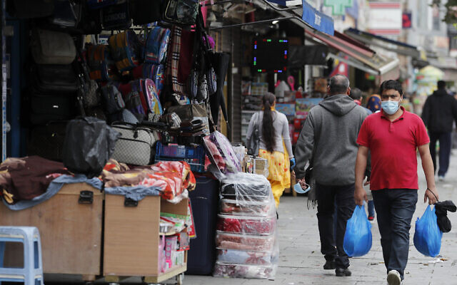 Shoppers walk past opened retail shops as coronavirus restrictions on non-essential retailers were lifted in London, Friday, June 19, 2020. (AP Photo/Frank Augstein)