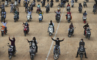 Faithful sit on their two-wheelers and pray as they attend a drive-in mass in an open area of Bethel AG Church as part of maintaining social distancing to prevent the spread of coronavirus in Bengaluru, India, Sunday, June 21, 2020. India is the fourth hardest-hit country by the COVID-19 pandemic in the world after the US, Russia and Brazil. (AP Photo/Aijaz Rahi)