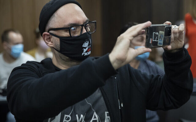 Russian theatre and film director Kirill Serebrennikov wearing a face mask with a portrait of Russian rock singer Viktor Tsoi, takes photos of the media prior to his hearing in a court in Moscow, Russia, June 22, 2020 (AP Photo/Pavel Golovkin)