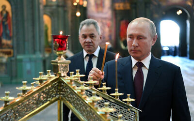 Russian President Vladimir Putin, right, lights a candle with Russian Defense Minister Sergei Shoigu in the background, at the Main Cathedral of the Russian Armed Forces, June 22, 2020. (Alexei Nikolsky, Sputnik, Kremlin Pool Photo via AP)