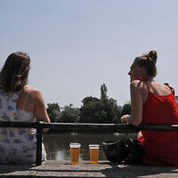Two women sit with take away drinks from a pub on the banks of the river Thames in London, Tuesday, June 23, 2020. (AP/Frank Augstein)