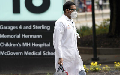 A healthcare professional walks through the Texas Medical Center on June 25, 2020, in Houston. (AP Photo/David J. Phillip)