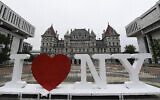 "In this June 18, 2019, file photo, a new promotional ""I Love NY"" sign sits in the Empire State Plaza for installation in front of the New York state Capitol in Albany, New York (AP Photo/Hans Pennink, File)"