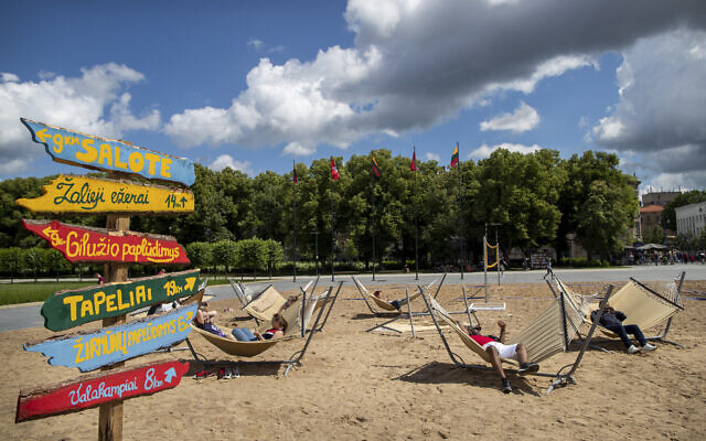 People sunbathe on an artificial beach in Vilnius, Lithuania, Tuesday, June 30, 2020. (AP/Mindaugas Kulbis)