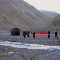In this May 5, 2013 file photo, Chinese troops hold a banner which reads: 'You've crossed the border, please go back,' in Ladakh, India (AP Photo/File) INDIA OUT