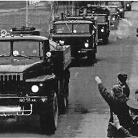 Residents cheer and wave as a column of armed vehicles carrying former Soviet troops leaves Vilnius, March 3, 1992. (Mendaugus Kublis/AP)