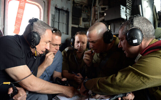 Illustrative: Prime Minister Benjamin Netanyahu (L) looks at a map with military officers as he rides on a helicopter to see a newly built portion of the West Bank security barrier, July 20, 2016. (Haim Zach/GPO/Flash90)