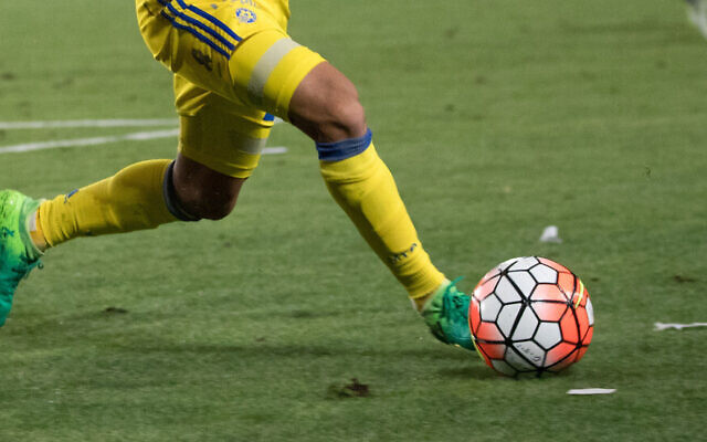 A Maccabi Tel Aviv player kicks a ball during a match (Yonatan Sindel/Flash90)