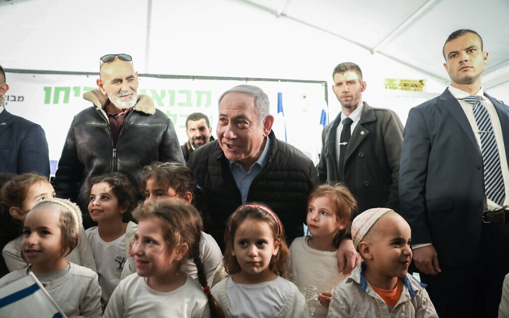 Prime Minister Benjamin Netanyahu poses with children during a tree planting event for the Jewish holiday of Tu Bishvat, in the West Bank settlement of Mevo'ot Yericho on February 10, 2020. (Flash90)