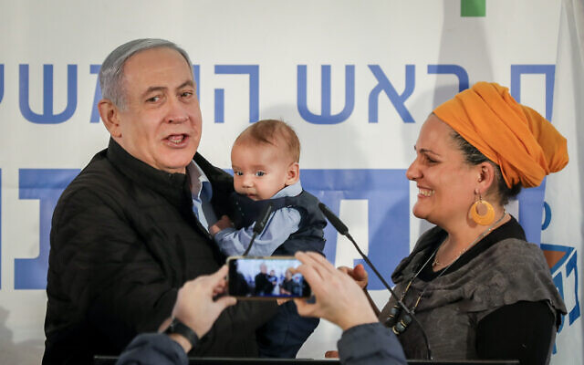 Prime Minister Benjamin Netanyahu holds a baby named after him during a tree planting event for the Jewish holiday of Tu Bishvat, in the West Bank settlement of Mevo'ot Yericho on February 10, 2020. (Flash90)