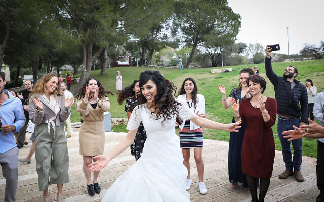 Hananel Even Hen and Shiran Habush celebrate during their wedding at a public park in the settlement of Efrat, in Gush Etzion, March 15, 2020. (Gershon Elinson/Flash90)