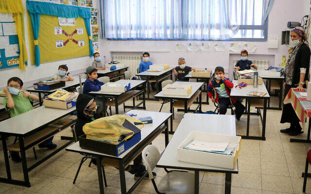 Students at the Orot Etzion school in the West Bank settlement of Efrat wear protective face masks as they return to class for the first time since schools were closed due to the coronavirus pandemic. (Gershon Elinon/Flash90)