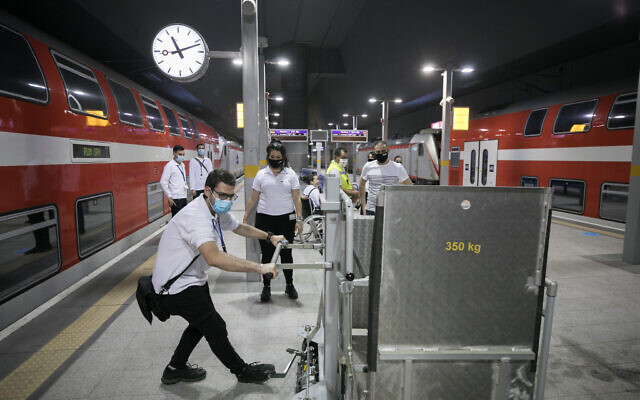 Train station staff and workers are seen receiving training instructions at Yitzhak Navon train station in Jerusalem, before a possible reopening order from the government on May 14, 2020. (Olivier Fitoussi/Flash90)
