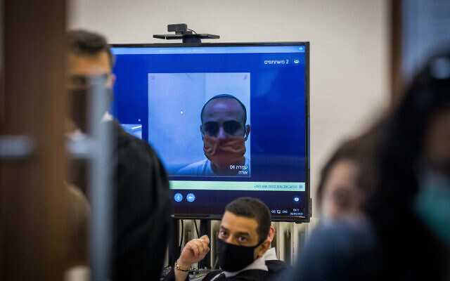 Eliran Malul, charged with stabbing his wife Michal Sela to death at their home in Ramat Motza, seen via a video link during a hearing at the Jerusalem District Court on May 26, 2020. (Yonatan Sindel/Flash90)