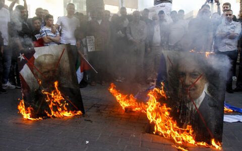 Palestinian demonstrators burn pictures of US President Donald Trump and Israeli Prime Minister Benjamin Netanyahu during a protest against Israel annexation plans, in the West Bank city of Nablus, May 30, 2020. (Nasser Ishtayeh/Flash90)