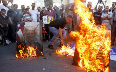 Palestinian demonstrators burn pictures of US President Donald Trump and Israeli Prime Minister Benjamin Natanyahu during a protest against Israel annexation plans, in the West Bank city of Nablus, May 30, 2020. (Nasser Ishtayeh/Flash90)