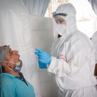 Magen David Adom medical workers take samples to test for the novel coronavirus in South Tel Aviv on June 2, 2020. (Miriam Alster/Flash90)