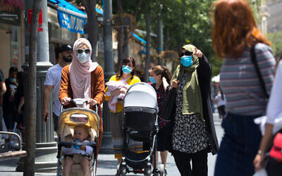 Israelis wearing face masks for fear of coronavirus walk in Jerusalem's city center after the government eased some lockdown measures that it had imposed in order to stop the spread of the coronavirus, on June 02, 2020. (Olivier Fitoussi/Flash90)