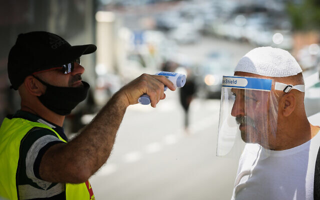 A man checks the temperature of a customer to see if he has a fever at the entrance to a market in the northern Israeli city of Safed, on June 3, 2020. (David Cohen/ Flash90)