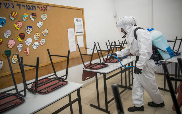 Cleaning workers disinfect a classroom at the Gymnasia Rehavia high school in Jerusalem on June 3, 2020 (Yonatan Sindel/Flash90)