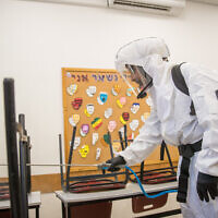 A cleaning workers disinfects a classroom at the Gymnasia Rehavia high school in Jerusalem on June 3, 2020. (Yonatan Sindel/Flash90)