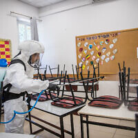 A cleaning worker disinfects a classroom in Jerusalem on June 3, 2020. (Yonatan Sindel/Flash90)
