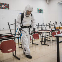 Cleaning workers disinfect a classroom at the Gymnasia Rehavia high school in Jerusalem on June 3, 2020. (Yonatan Sindel/Flash90)