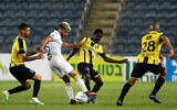 Illustrative: A Maccabi Tel Aviv player, in white, dribbles the ball between opposing players during a match against Beitar Jerusalem in Jerusalem on June 8, 2020. (Flash90)