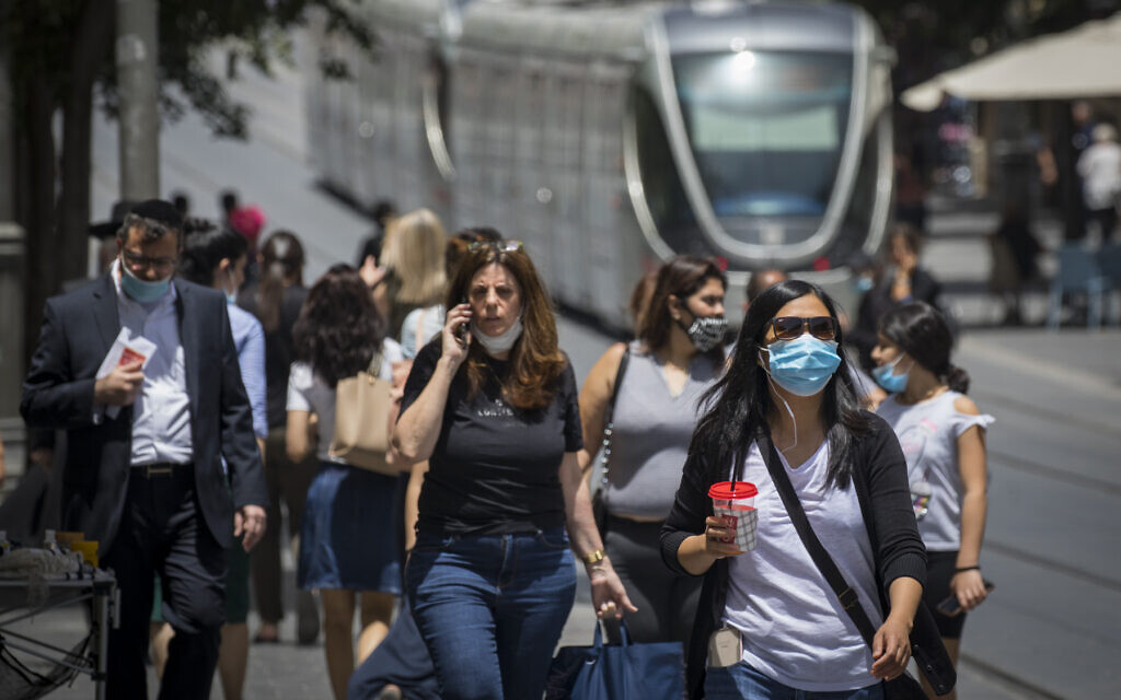 A woman uses a cellphone as people wear face masks for fear of coronavirus in downtown Jerusalem, June 8, 2020. (Olivier Fitoussi/Flash90)