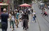 People wearing face masks walk in Jerusalem on June 8, 2020. (Olivier Fitoussi/ Flash90)