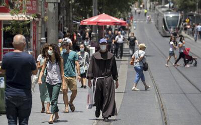 People wearing face masks walk in Jerusalem on June 8, 2020. (Olivier Fitoussi/ Flash90)