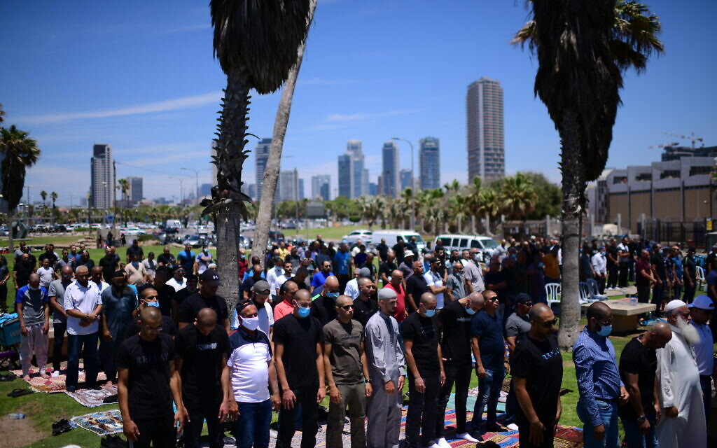 Arabs citizens pray prior to a protest against the decision by the Tel Aviv Municipality to demolish an old Muslim burial ground which was discovered after plans had been made to build a new homeless shelter and commercial space at the site. June 12, 2020. (Tomer Neuberg/FLASH90)  îúôìì