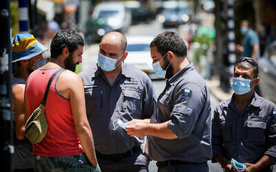 Inspectors talk to people who are not wearing face mask in the northern Israeli city of Tzfat, June 15, 2020. (David Cohen/Flash90)