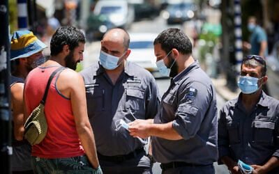 Inspectors talk to a man not wearing a face mask in the northern city of Safed on June 15, 2020. (David Cohen/ Flash90)